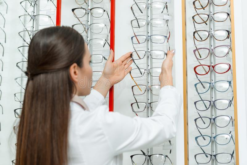 selektiv fokus av optometrikern som tar glasögon från hylla arkivfoto