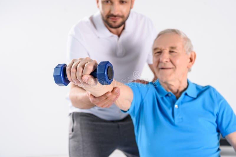 selektiv fokus av rehabiliteringterapeuten som hjälper den höga mannen som övar med hanteln arkivbild