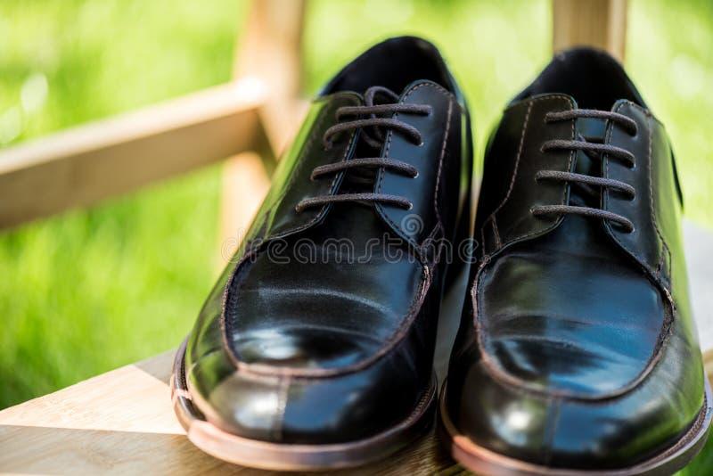 selektiv fokus av svarta läderskor på trätrappa med gräsplan royaltyfria foton