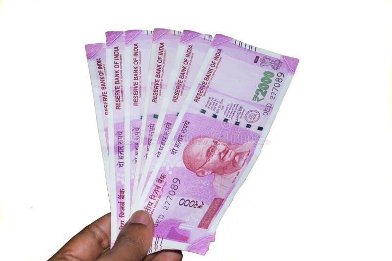 Selektiv fokus: Hand som rymmer indiska 2000 rupieanmärkningar mot vit bakgrund Stäng sig upp av den nya rupiesedeln 2000 på man arkivfoton