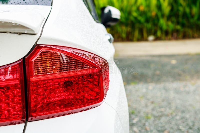 Selektiv fokus och Closeup av bakre billjus med regndroppewat arkivfoton
