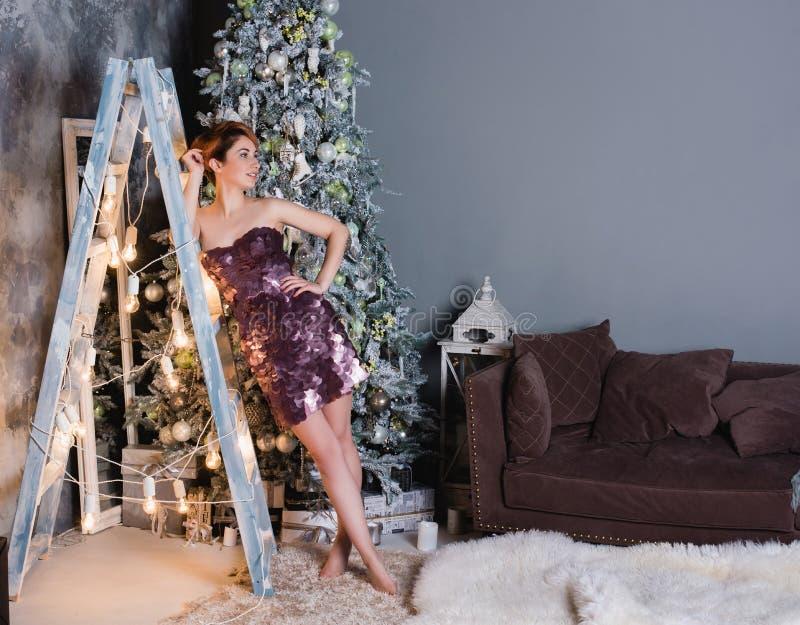Selektiv fokus på den le härliga kvinnan som bär den trevliga aftonklänningen och gratulerar oss med det nya året royaltyfri bild