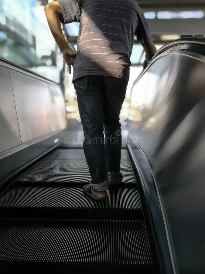 Selektiv fokus på den manliga baken, manställning på rulltrappan royaltyfri bild