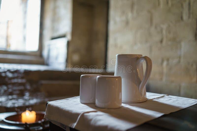 Selektiv fokus på den vita keramiska tekrukan och tekoppar med ljus royaltyfria foton