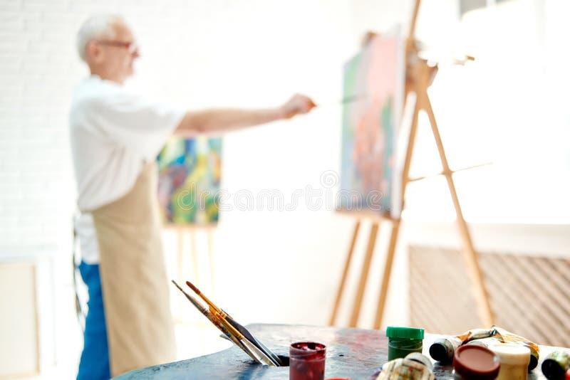 Selektiv fokus på förgrund med paletten av målarfärger och borstar royaltyfria foton