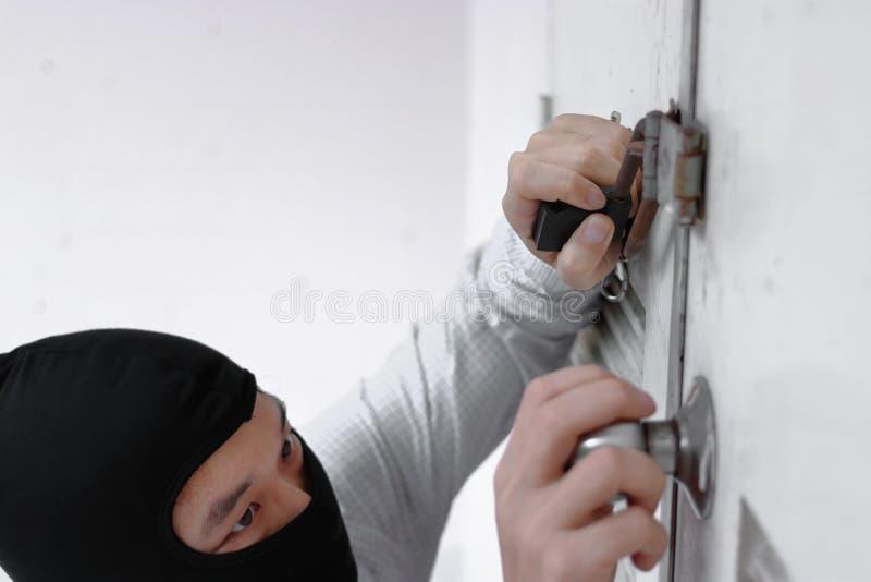 Selektiv fokus på händer av den maskerade tjuven i den svarta balaclavaen som försöker att bryta in i hus royaltyfri fotografi