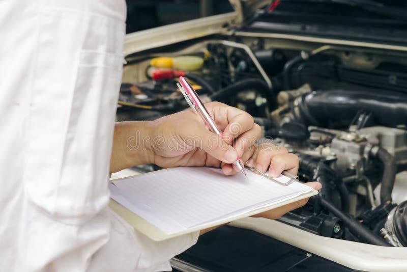Selektiv fokus på händer av den yrkesmässiga unga asiatiska mekanikermannen i enhetlig handstil på skrivplattan mot bilen i öppen arkivbild
