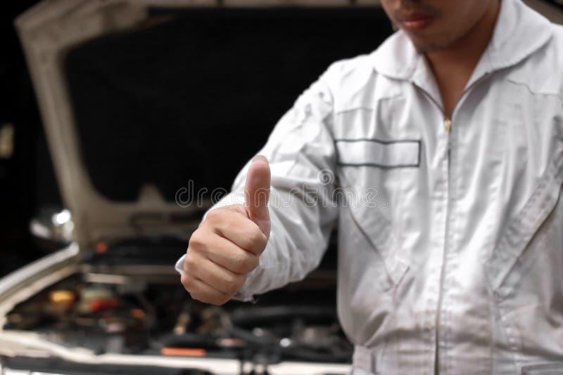 Selektiv fokus på händer av den yrkesmässiga unga tummen för mekanikermanvisning upp som tecken av framgång med bilen i öppen huv royaltyfri foto