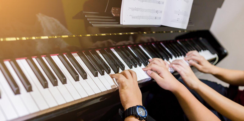 Selektiv fokus som ska föreställas av den unga kvinnan som undervisar en pojke att spela pianot med musikbeteckningssystemet royaltyfri bild