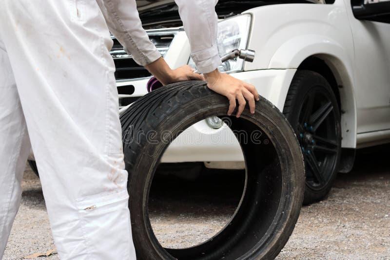 Selektiver Fokus auf Händen des Berufsmechanikers im einheitlichen haltenen Schlüssel und im Reifen am Reparaturgaragenhintergrun stockfoto