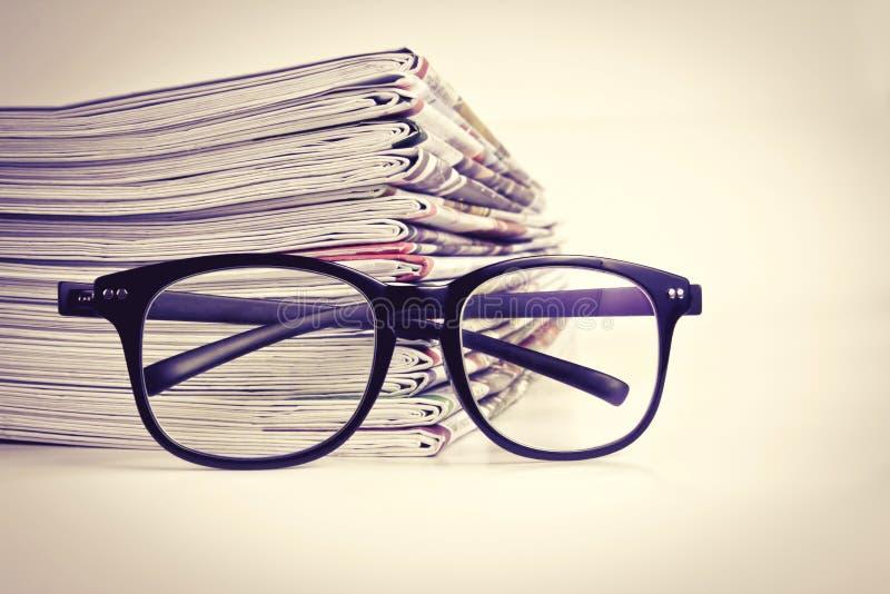 Selektiver Fokus auf Lesebrillen mit dem Stapeln der Zeitung lizenzfreies stockfoto
