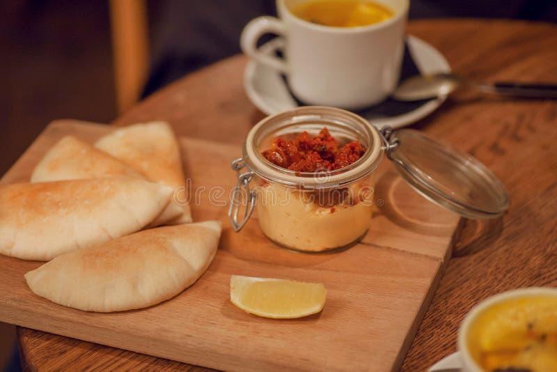 Selektiver Fokus auf Schnellimbiß innerhalb eines Cafés mit Snäcken Aperitifhummus, -Pittabrot und -tee mit Zitrone zum Frühstück stockfotografie