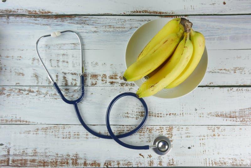 Selektiver Fokus des Bündels der Bananen und des Stethoskops stockbild