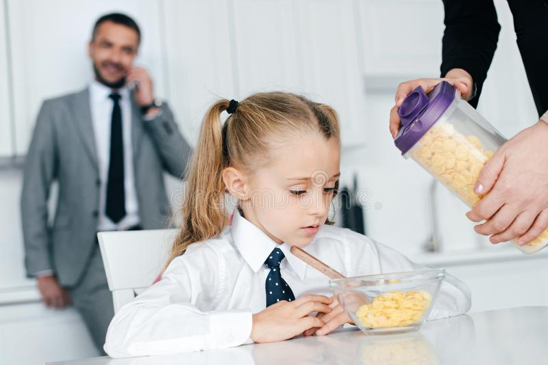 selektiver Fokus des Kindes in der Schuluniform bei Tisch mit Frühstück und Eltern zu Hause zurück zu stockfotografie