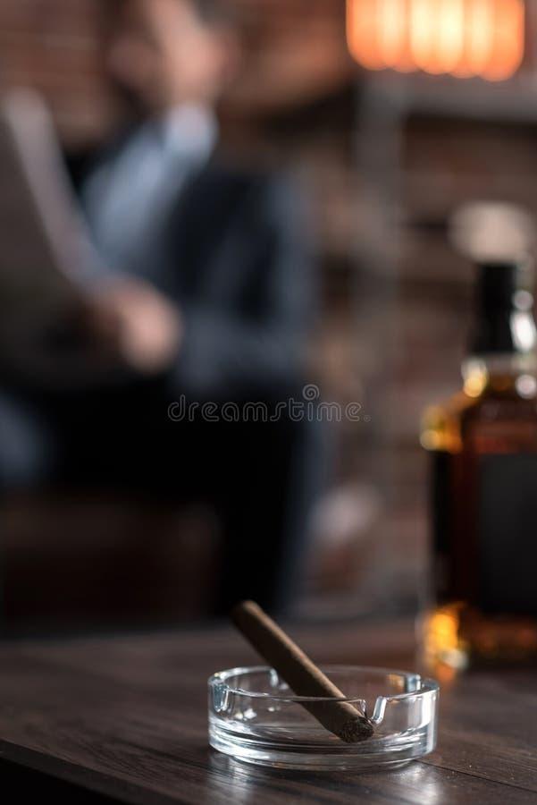 Selektiver Fokus einer Zigarre, die nahe der Flasche liegt lizenzfreie stockbilder