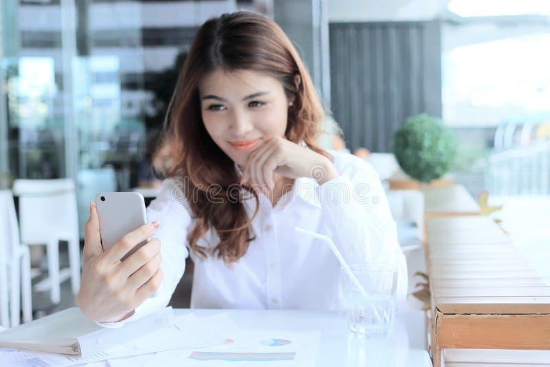 Selektiver Fokus am intelligenten Mobiltelefon in den Händen der hübschen Asiatin zwischen selfie verwischte Hintergrund oder das stockbilder
