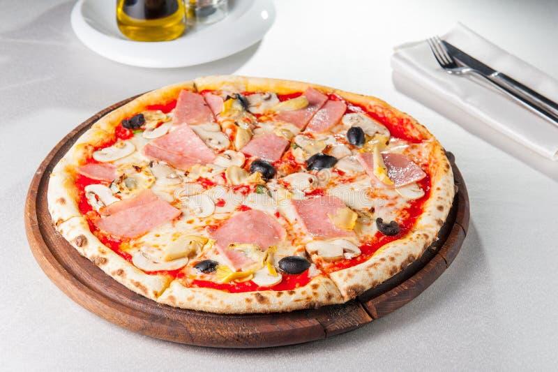 Selektiver Fokus köstliche Fleisch-Pizza mit Speck, Hühnerleiste, Pilzen in Scheiben und Oliven auf dem hölzernen Brett auf dem s lizenzfreie stockfotos