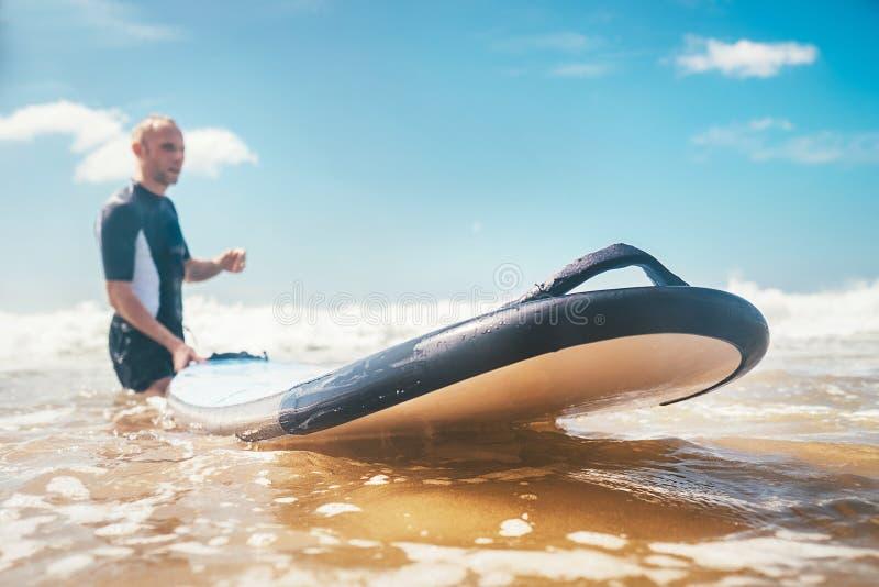 Selektiver Fokus mit breiter offener Öffnung des langen Brandungsbrettes auf Meereswogen mit unfocused Surfer des jungen Mannes a lizenzfreies stockbild