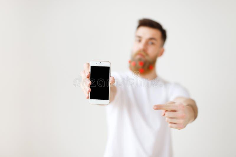 Selektiver Fokus Modernes intelligentes Telefon mit leerem Bildschirm in den Händen des Mannes s Bärtiger stilvoller Mann annonci stockfotografie