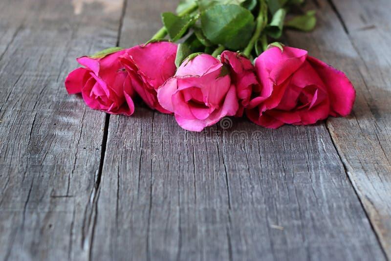 Selektiver Fokus und flache Schärfentiefe des Blumenstraußes der roten Rosen auf altem Hintergrund des hölzernen Brettes mit Kopi lizenzfreie stockfotos