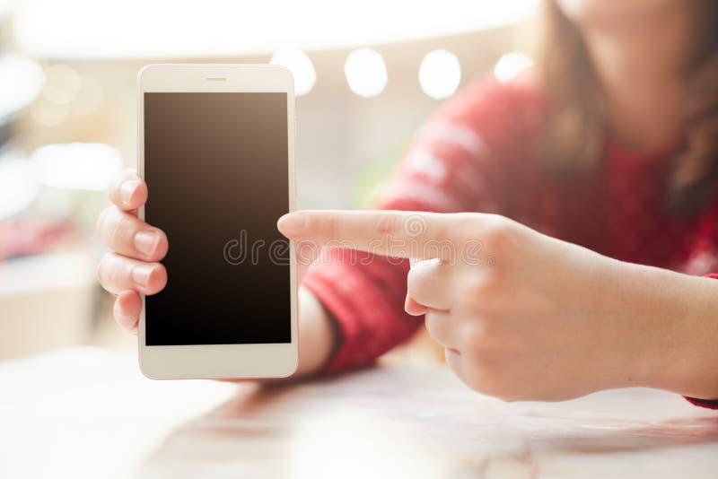 Selektiver Fokus Unerkennbare Frau hält modernes weißes intelligentes Telefon in der Hand, Punkte mit dem Finger am leeren Kopien stockbild