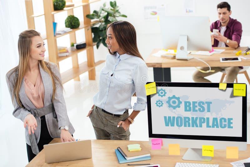 selektiver Fokus von den multikulturellen Geschäftsfrauen, die zusammen Laptop am Arbeitsplatz in der besten Arbeitsplatzaufschri stockfotografie
