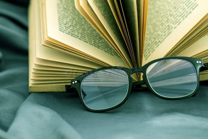 Selektiver Fokus von Lesungsbrillen mit geöffnetem Buch stockfotos