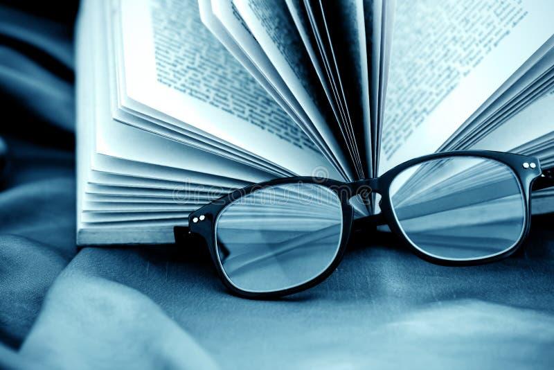 Selektiver Fokus von Lesungsbrillen mit geöffnetem Buch lizenzfreie stockfotos