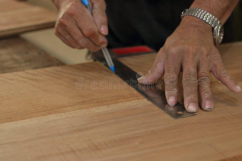 Selektivt fokusera och bli grund djup av sätter in Linjal som tar mätning på en träplanka med handen av den höga snickaren i semi royaltyfri bild