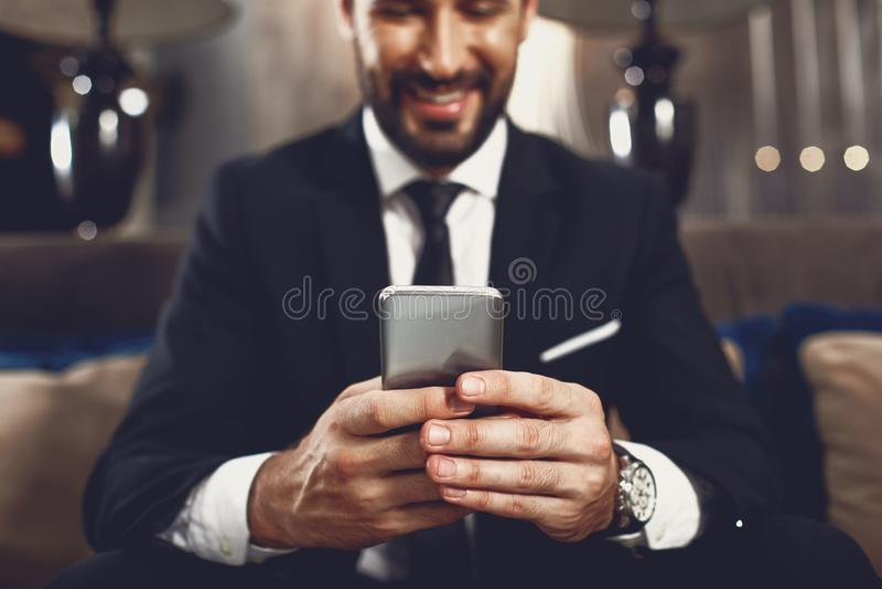 Selektywne skupienie nowoczesnego smartfona w rękach uśmiechniętego człowieka obrazy royalty free