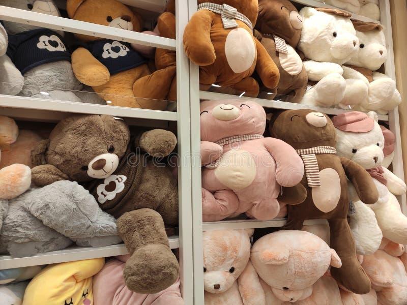 Seletivos focalizados de ursos de peluche e de outros brinquedos macios dos caráteres foram indicados em prateleiras para a venda fotografia de stock royalty free