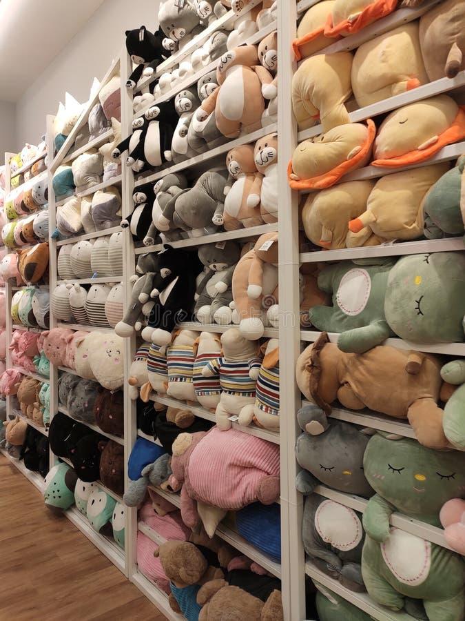 Seletivos focalizados de ursos de peluche e de outros brinquedos macios dos caráteres foram indicados em prateleiras para a venda imagens de stock