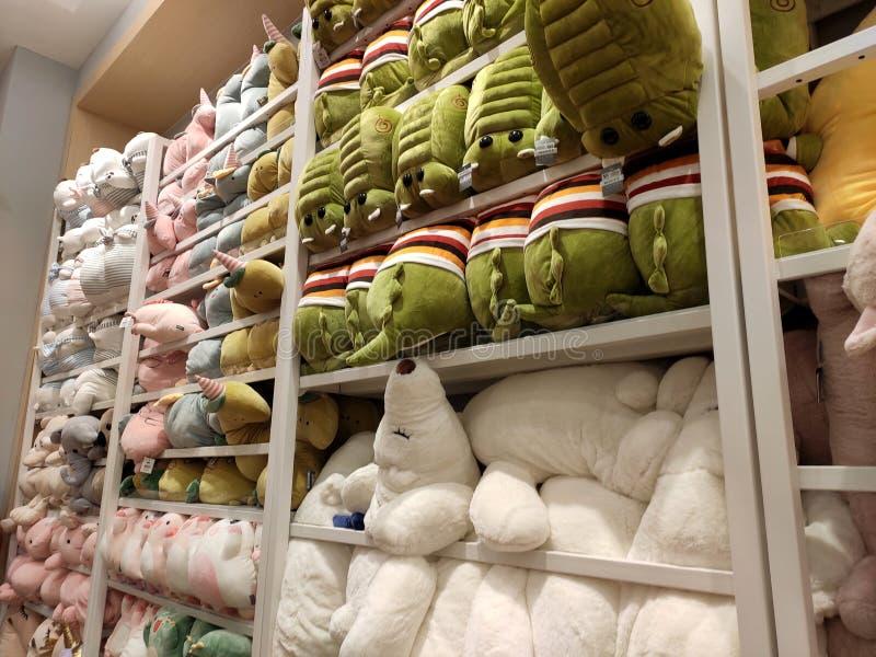 Seletivos focalizados de ursos de peluche e de outros brinquedos macios dos caráteres foram indicados em prateleiras para a venda fotos de stock