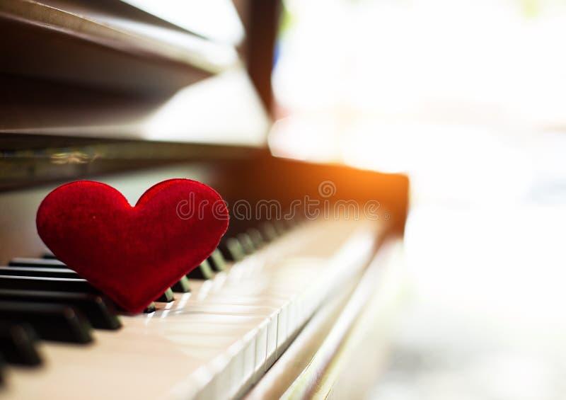 In selettivo di piccolo cuore rosso messo sulle chiavi del piano, la riflessione di luce solare è brillante al piano fotografie stock libere da diritti