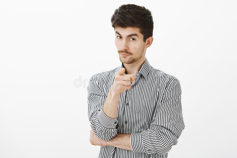 Selezionamento voi per lavorare nel mio gruppo dei capi Bello uomo astuto intrigante in camicia a strisce, indicante alla macchin fotografie stock