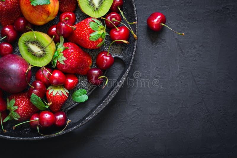Selezione dei frutti e delle bacche stagionali su un piatto della ghisa A immagine stock