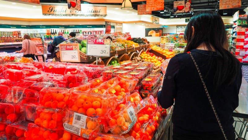 Selezione della donna frutta fresca nel dipartimento dei prodotti della drogheria e nel metterlo nel sacchetto di plastica La gio immagini stock