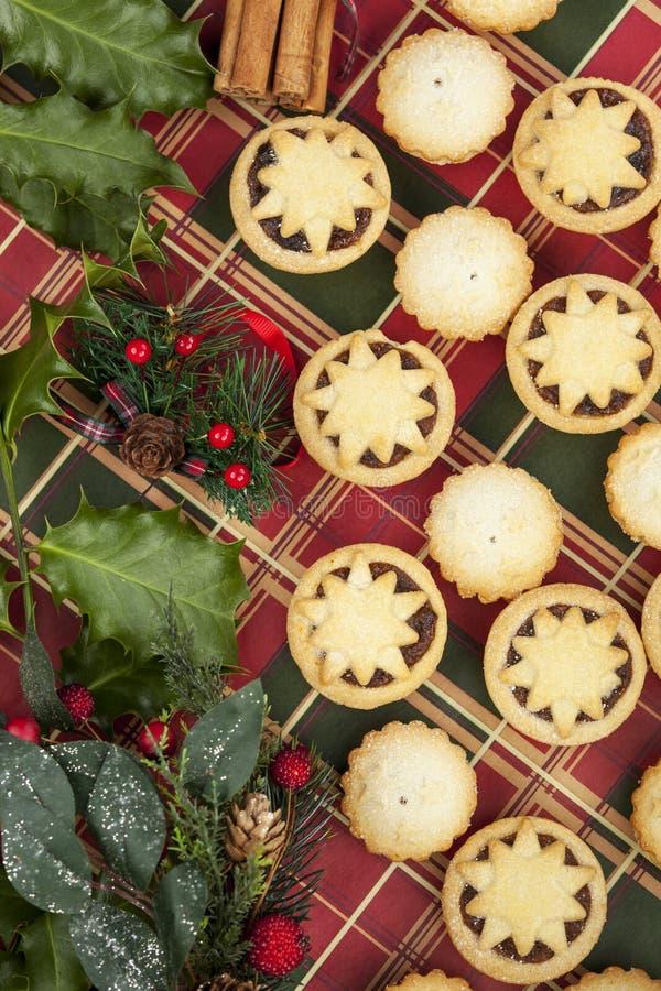 Selezione di Natale di mini mince pie e foglie dell'agrifoglio fotografia stock