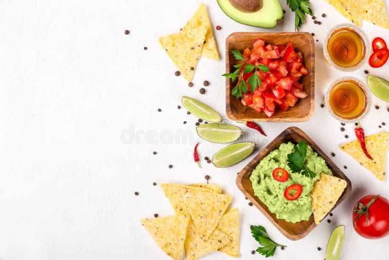 Selezione messicana dell'alimento: guacamole della salsa, salsa, patatine fritte e colpi di tequila con calce su fondo bianco immagini stock