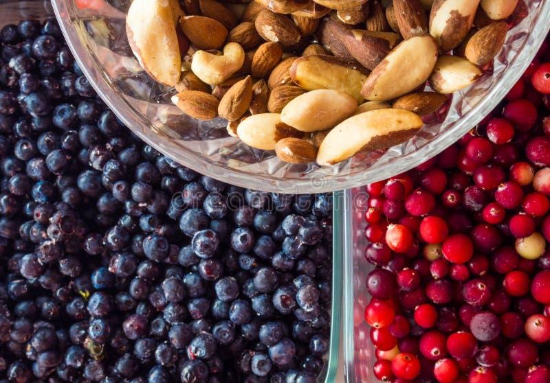 Selezione pulita di cibo dell'alimento sano: superfood, nocciole, bacche fondo, alimenti per cuore sano immagini stock
