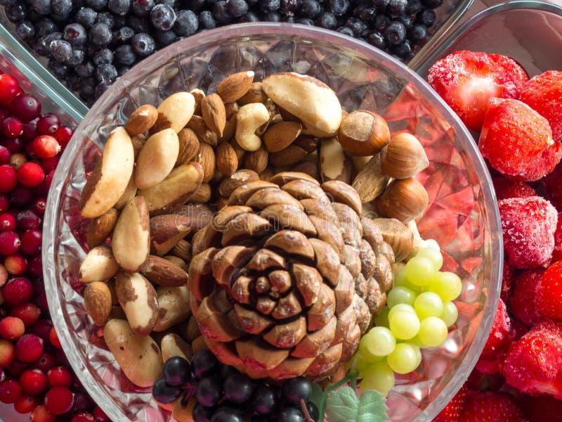 Selezione pulita di cibo dell'alimento sano: superfood, nocciole, bacche fondo, alimenti per cuore sano fotografie stock