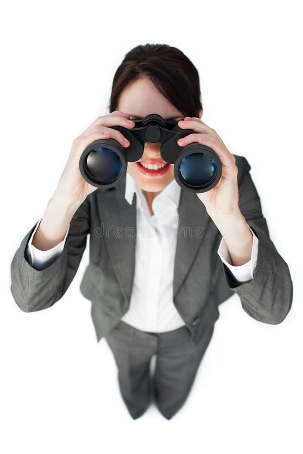 Self-assured businesswoman with binoculars stock photo