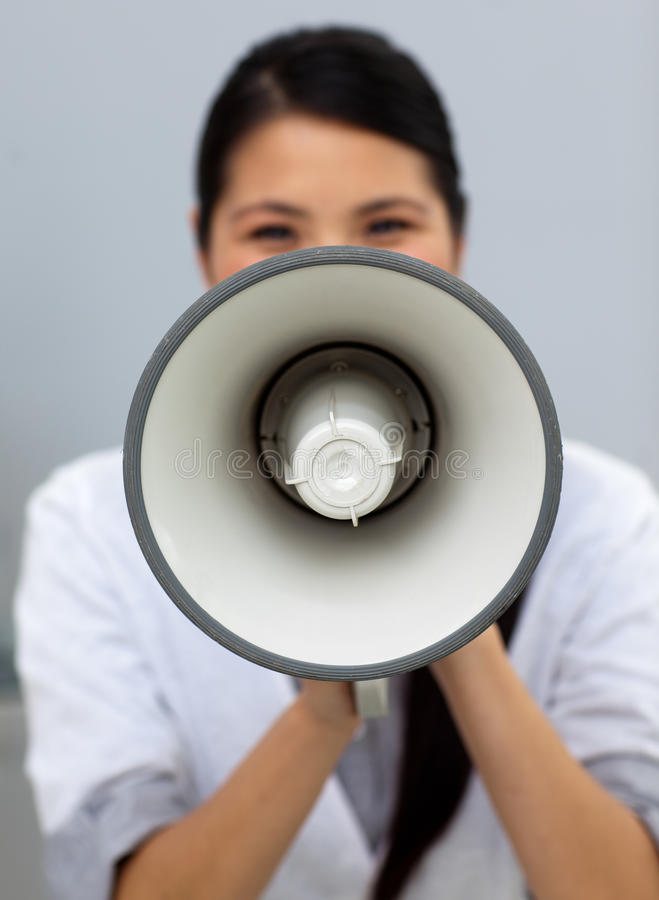 Self-assured businesswoman shouting instructions. Through a megaphone stock image