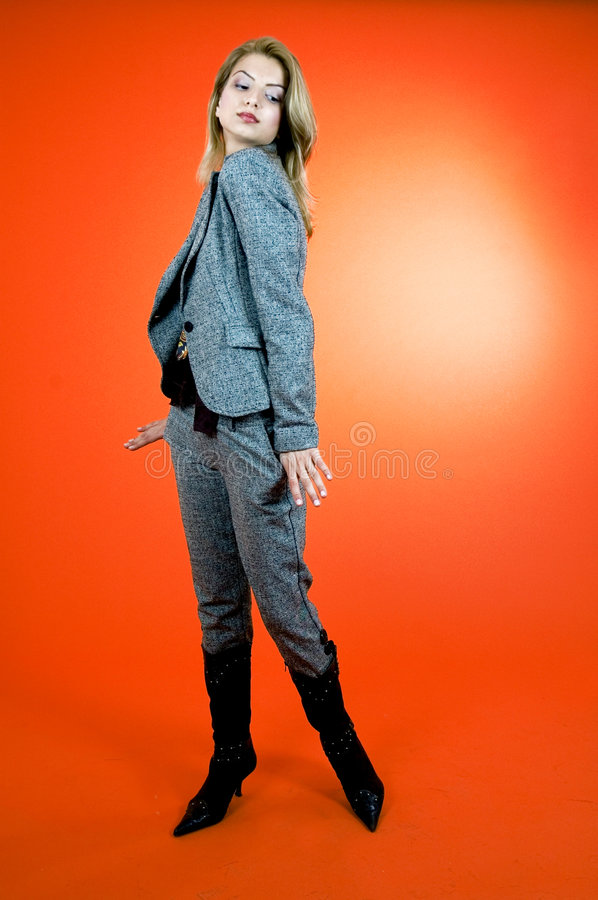 Self-Assured Woman. Portrait of a young woman in a self-assured pose. Taken in studio with orange background royalty free stock image