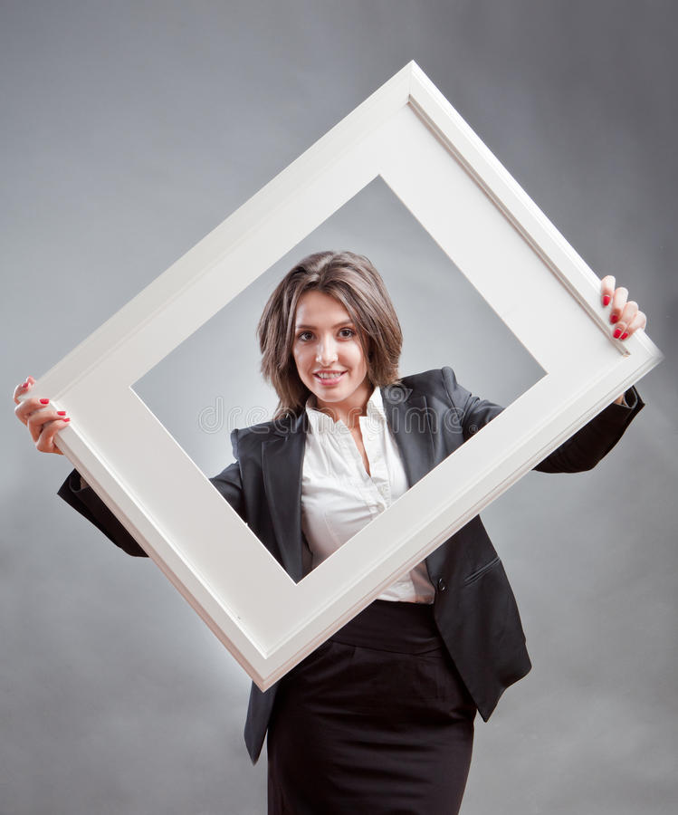 Self branding. Concept with young office woman holding a photo frame advertising herself royalty free stock image