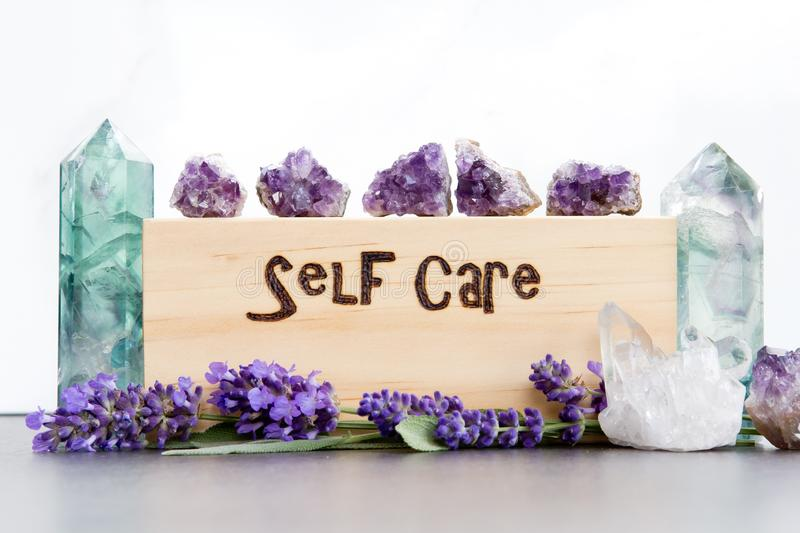 Self Care - word burnt in wood with purple lavender flowers, amethyst, fluorite and quartz crystals on slate with white background. Self Care - word burnt in stock photo
