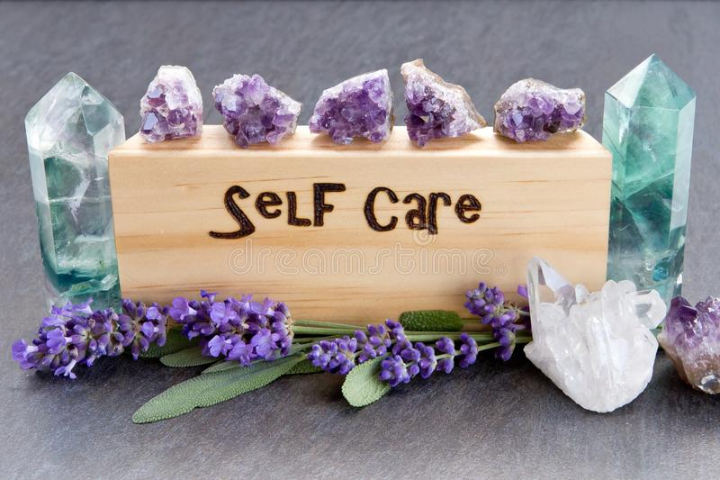 Self Care - word burnt in wood with purple lavender flowers, amethyst, fluorite and quartz crystals on slate background. Self Care - word burnt in wood with royalty free stock photography