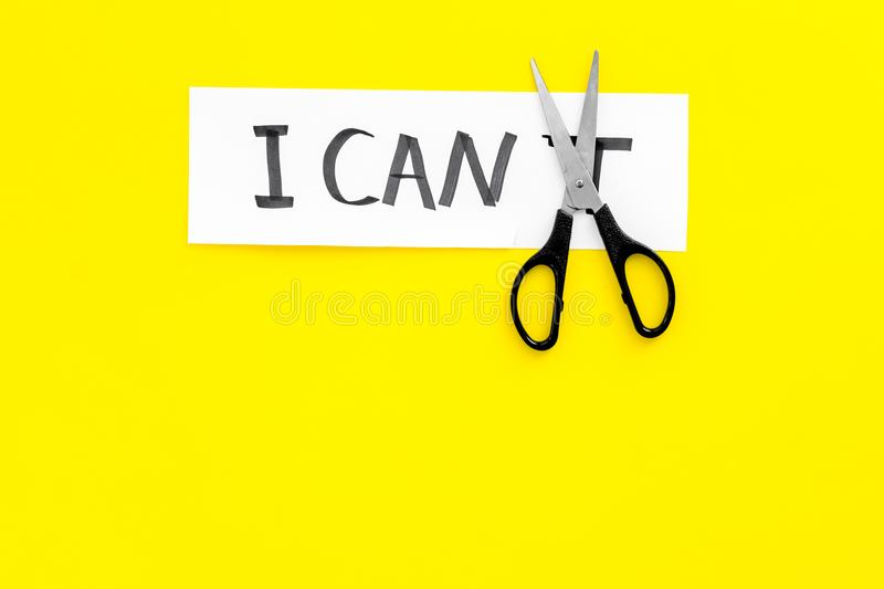 Self confidence concept. Cutting the letter t of written word I can`t by sciccors. Yellow background top view copy space. Self confidence concept. Cutting the stock photography