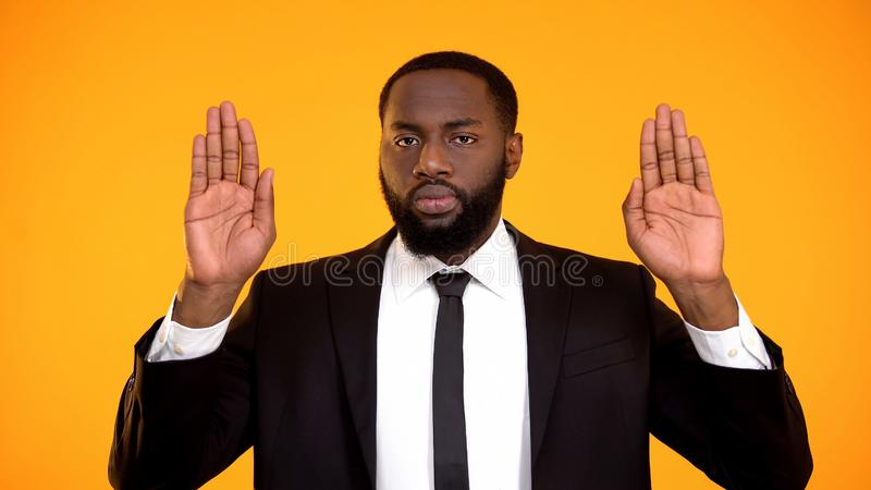 Self-confident black businessman male showing stop sign to fraud and corruption stock image