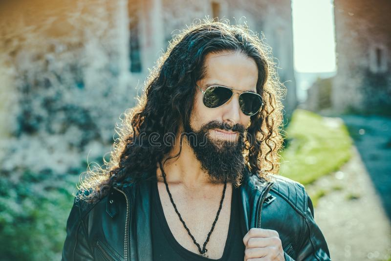 Self confident handsome man in sunglasses. Macho man walking outside alone. Stylish young fashionable man with long wavy stock images
